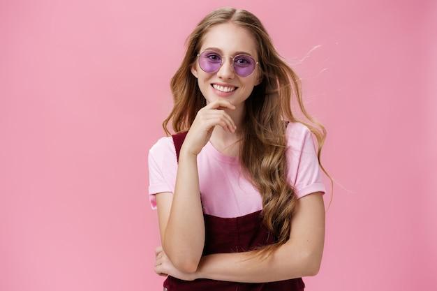 Schönheit, stil und modekonzept. porträt einer charmanten, selbstbewussten europäischen frau mit natürlichem, gewelltem haar in sonnenbrille und overall, die das kinn berührt, amüsiert und breit gegen die rosa wand lächelt.