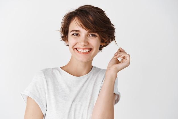 Schönheit und hautpflege. porträt einer glücklichen und selbstbewussten frau mit natürlicher schönheit ohne make-up, berührender haarsträhne und lächelnder, weißer wand