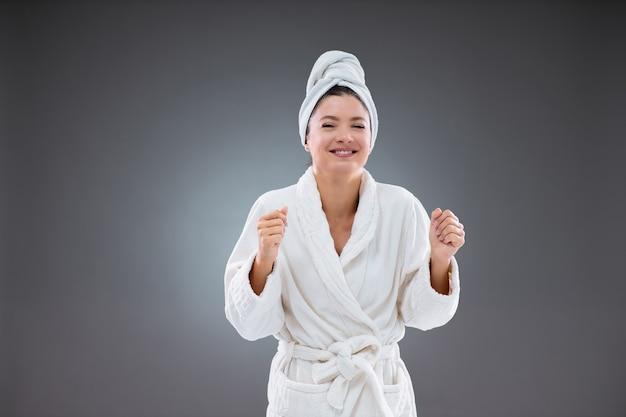 Schönheit und komfort. eine glückliche frau mittleren alters mit sauberer gesichtshaut in einem weißen bademantel und in ein weißes handtuch gewickeltem haar steht vor einer grauen wand. sie hält ihre arme an den ellbogen gebeugt