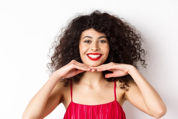 Schönheit und make-up. hübsche dame mit lockigem haar, roten lippen und weißen zähnen, lächelnd und perfektes gesicht zeigend, stehend auf weißem hintergrund.