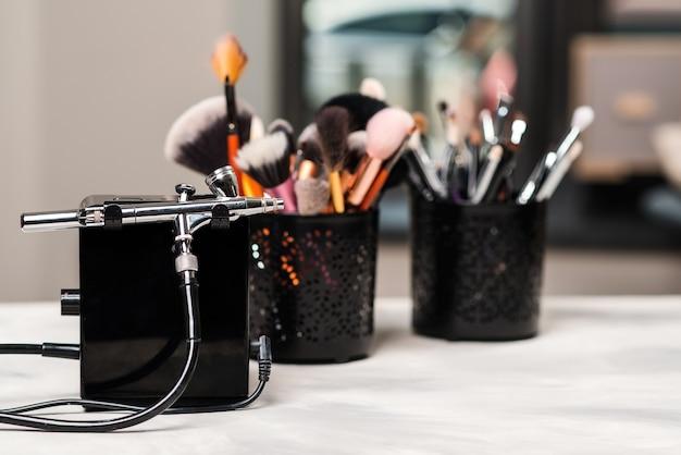 Schönheit und mode. make-up-werkzeuge und pinsel am künstlerarbeitsplatz. make-up-produkte eingestellt. schönheitssalon behandlung. airbrush für make-up. moderner schönheitssalon