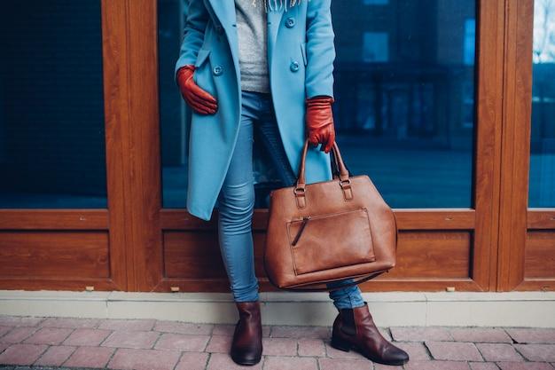 Schönheit und mode. tragender mantel und handschuhe der stilvollen modernen frau, braune taschenhandtasche halten