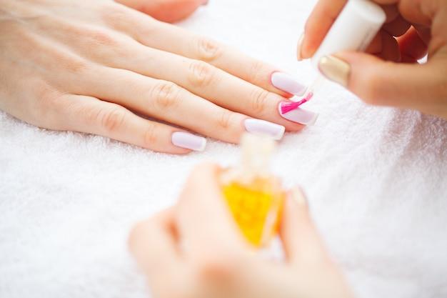 Schönheit und pflege. maniküre-meister, der nagellack im schönheitssalon aufträgt. schöne frauenhände mit perfekter maniküre. spa maniküre
