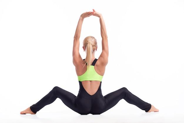 Schönheit von hinten. rückansicht studioaufnahme einer starken und fitten sportlerin, die mit erhobenen armen und gespreizten beinen sitzt