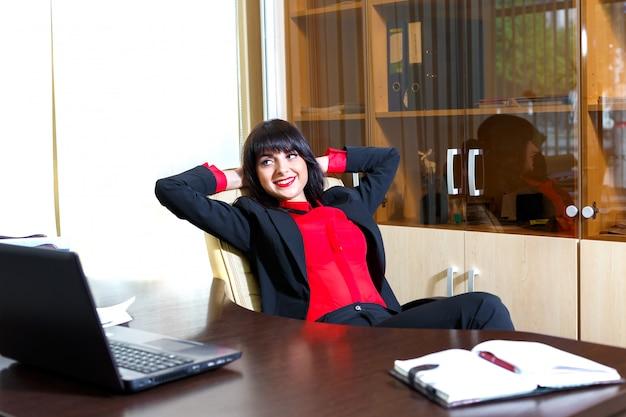 Schönheiten, die am tisch im büro sich entspannen