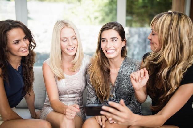 Schönheiten, die handy betrachten und mit einander sprechen