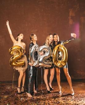 Schönheiten, die neues jahr feiern glückliche herrliche mädchen in den stilvollen sexy parteikleidern, die gold- und silber-2020-ballone, spaß an silvesterabend-party habend halten selfie oder video für instagram machen