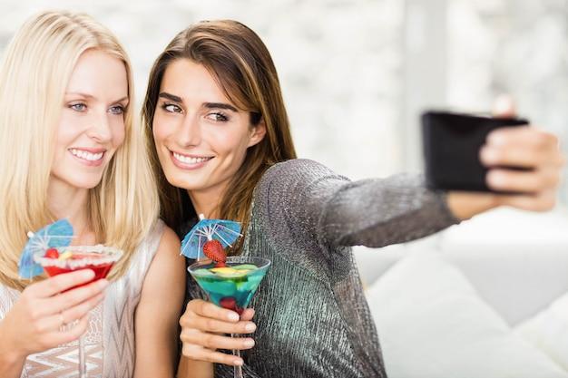 Schönheiten, die selfie mit handy nehmen und mocktail essen