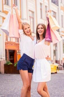 Schönheiten mit einkaufstüten. zwei attraktive junge frauen, die einkaufstüten halten und lächeln, während sie im freien stehen