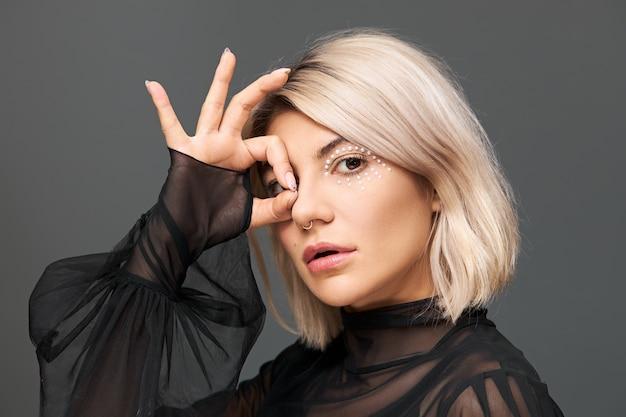 Schönheits-, glamour-, luxus- und modekonzept. profilaufnahme der attraktiven kühlen jungen frau in der stilvollen transparenten schwarzen bluse mit fackeln, die isoliert, daumen und zeigefinger im ok-zeichen verbindend aufwirft