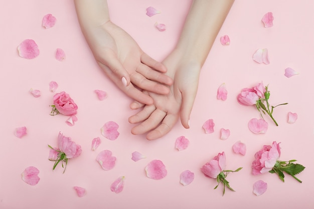 Schönheits-hand einer frau mit roten blumen liegt auf tabelle auf rosa papier