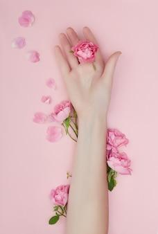 Schönheits-hand einer frau mit roten blumen liegt auf tabelle, rosa papieroberfläche. naturkosmetikprodukt und handpflege, feuchtigkeitsspendend und faltenreduzierend, hautpflege