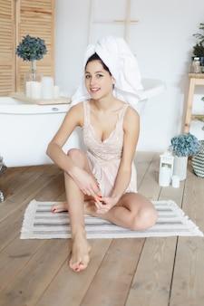 Schönheits-, hautpflege- und menschenkonzept - brünette schönheit mit weißem handtuch, das nur aus dem badezimmer kommt. heilbad, hydrotherapie, um die allgemeine spannung in körper und geist zu reduzieren. lächelnde frau