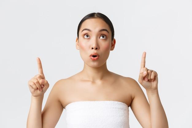 Schönheits-, kosmetologie- und spa-salon-konzept. erstaunt und beeindruckt hübsche asiatische frau im weißen handtuch, die fantastisches angebot sieht, finger zeigt und oben auf ansage schaut, weiße wand.