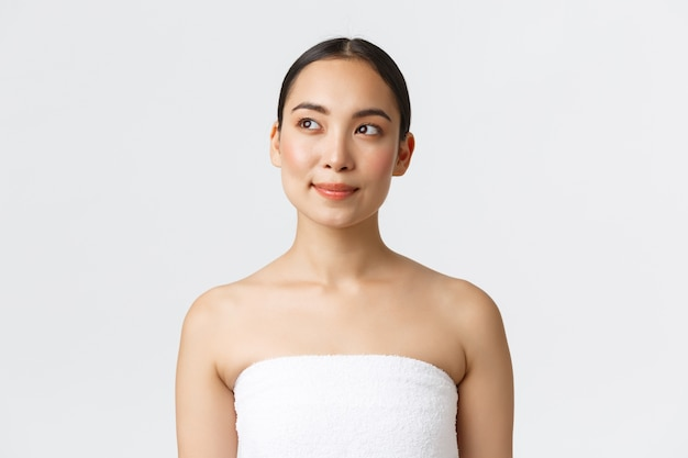 Schönheits-, kosmetologie- und spa-salon-konzept. junge schöne asiatische frau im handtuch, das links auf interessantes promo-angebot im schönheitssalon schaut, stehende weiße wand mit sauberer perfekter haut