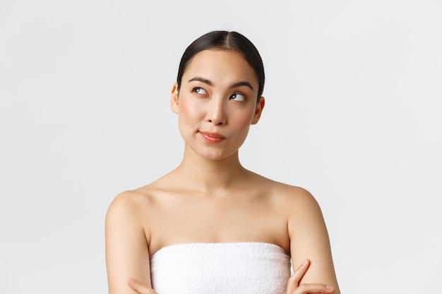 Schönheits-, kosmetologie- und spa-salon-konzept. nachdenkliche kreative asiatische frau im badetuch, die obere linke ecke schaut, denkt, entscheidung trifft, stehende weiße wand.