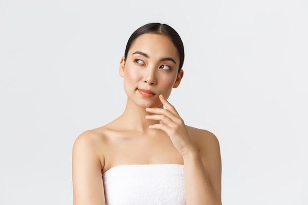 Schönheits-, kosmetologie- und spa-salon-konzept. nachdenkliche schöne asiatische frau im handtuch, die nach links schaut und denkt, nachdenkt oder wählt, welches verfahren in der schönheitsklinik genommen wird.