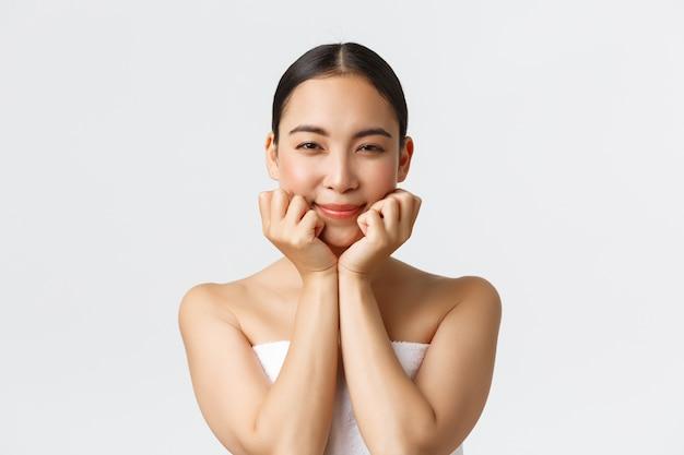 Schönheits-, kosmetologie- und spa-salon-konzept. nahaufnahme der herrlichen fröhlichen asiatischen frau im badetuch, kopf auf hände lehnend und lächelnd erfreut, behandlung der haut mit nachrichtenkosmetikprodukt