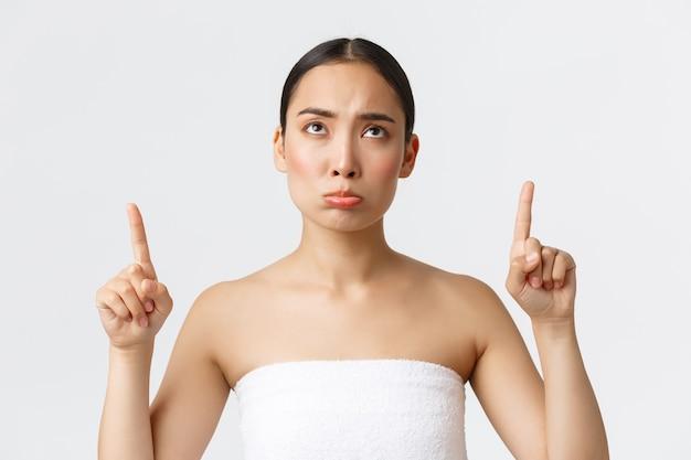 Schönheits-, kosmetologie- und spa-salon-konzept. schmollendes trauriges asiatisches mädchen im weißen handtuch schmollend und schauend, zeigte enttäuscht mit den fingern nach oben und beschwerte sich über schönheitssalon oder massagetherapie.