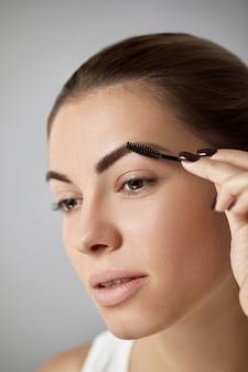 Schönheits-make-up. frau, die augenbrauennahaufnahme formt. mädchenmodell mit professionellem make-up, das augenbrauen konturiert