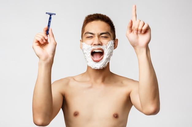 Schönheits-, menschen- und hygienekonzept. porträt eines begeisterten asiatischen nackten mannes im badezimmer, der während der rasur singt, das rasiermesser hält und tanzt, während er versucht, die höchste note zu erreichen, creme auf das gesicht aufzutragen