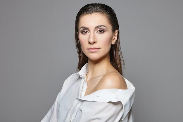 Schönheits-, mode-, stil- und kleidungskonzept. attraktives junges weibliches modell mit hellem make-up, das weißes hemd trägt, an grauer wand aufwirft, ruhiges, sicheres aussehen hat