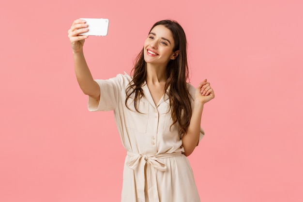 Schönheits-, mode- und frauenkonzept. anziehende junge weibliche frau, die selfie im neuen kleid, neues foto online bekannt gebend, lächelnde zarte und nette kamera nimmt und stehen rosa