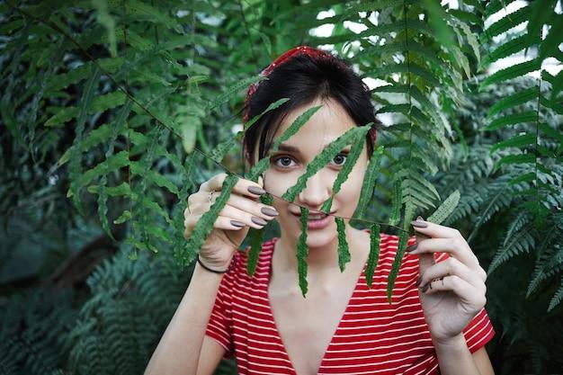 Schönheits-, natur- und frischekonzept. freundlich aussehendes junges kaukasisches weibliches modell, das sich in der wilden natur unter tropischen pflanzen entspannt, sich hinter frischem grünem blatt versteckt und mysteriöses lächeln hat