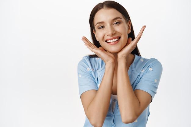 Schönheits- und frauenpflege. junge strahlende frau in den 30ern, die ihre natürliche gesunde, perfekte haut ohne make-up zeigt, keine falten, anti-aging-effekt des kosmetischen verfahrens