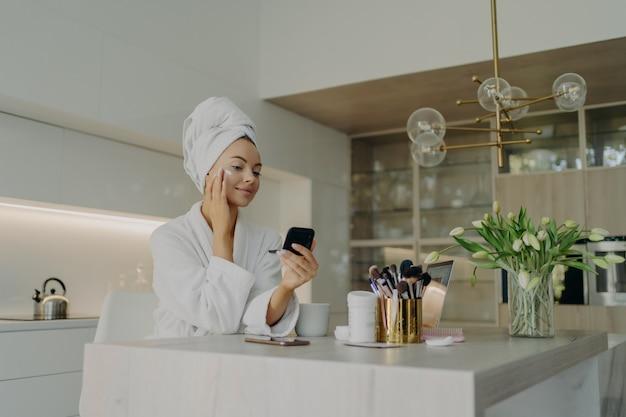 Schönheits- und gesichtspflegekonzept. junge hübsche frau im weißen bademantel, die kosmetisches produkt auf das gesicht aufträgt und in einen kompakten spiegel schaut, sich um ihre haut kümmert, während sie in der modernen küche zu hause sitzt