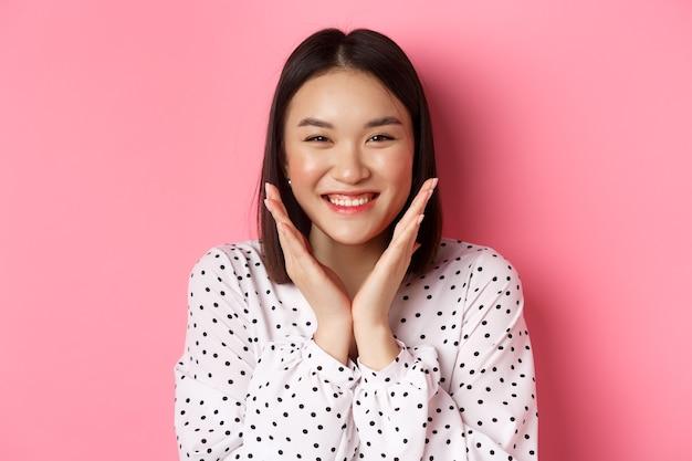 Schönheits- und hautpflegekonzept. nahaufnahme einer süßen asiatischen frau, die ein sauberes, perfektes gesicht zeigt und lächelt, glücklich in die kamera schaut und über rosafarbenem hintergrund steht