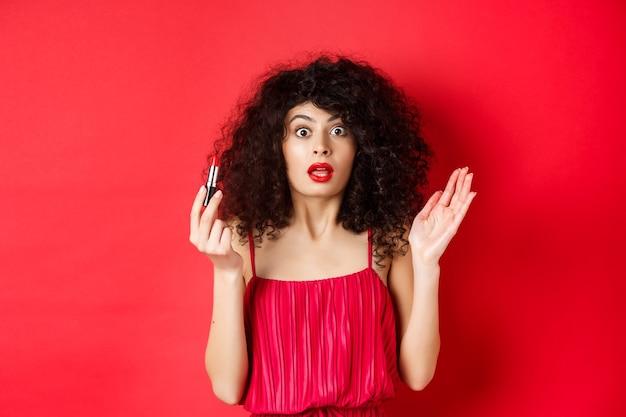 Schönheits- und make-up-konzept. aufgeregte frau mit lockigem haar, keuchend, als sie kamera betrachtet, roten lippenstift haltend, im kleid auf weißem hintergrund stehend.