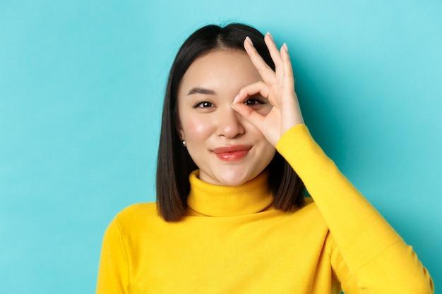 Schönheits- und make-up-konzept. schließen sie oben von sorglosem asiatischem mädchen, das ok-zeichen auf auge und lächeln zeigt, glücklich in die kamera schauend, über blauem hintergrund stehend.