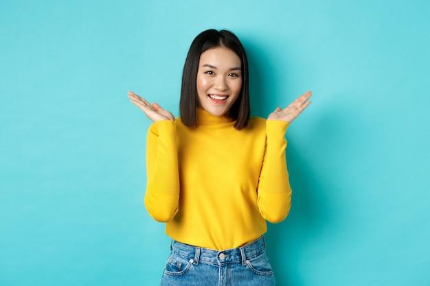 Schönheits- und modekonzept. attraktives japanisches mädchen hebt die hände und zeigt etwas, lächelt glücklich und schaut in die kamera, zeigt promo, blauer hintergrund.