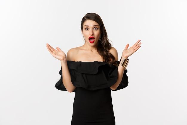 Schönheits- und modekonzept. aufgeregt schöne frau, die mit erstaunen überrascht, auf gute nachrichten reagiert, im schwarzen kleid mit make-up auf weißem hintergrund steht.