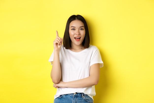 Schönheits- und modekonzept. aufgeregtes asiatisches mädchen, das den finger in der heureka-geste hebt, eine idee aufwirft und lächelt, auf gelbem hintergrund stehend