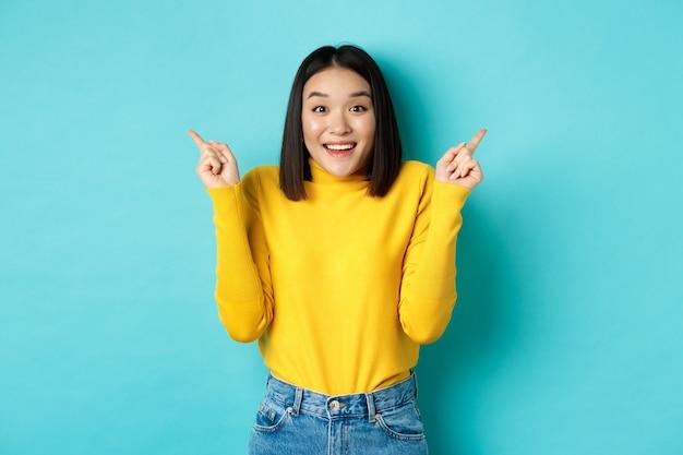 Schönheits- und modekonzept. fröhliches asiatisches mädchen, das zwei promo-angebote zeigt, mit dem finger seitlich auf die linke und rechte werbung zeigt und lächelt, auf blauem hintergrund stehend.