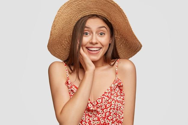 Schönheits- und modekonzept. glückliches überglückliches weibliches model kichert vor aufregung, hält hand auf wange
