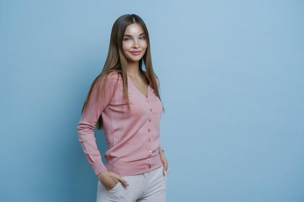 Schönheits- und modekonzept. junge attraktive frau fühlt sich selbstsicher und sorglos, gekleidet in stilvolles outfit, kümmert sich um haare
