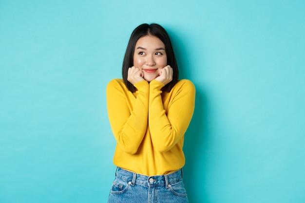 Schönheits- und modekonzept. schöne asiatische frau, die errötet und lächelt, verträumt nach links aussieht, sich etwas süßes vorstellt, vor blauem hintergrund stehend