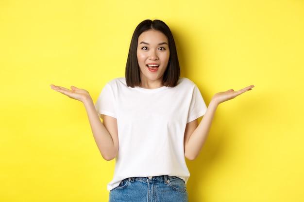 Schönheits- und modekonzept. überraschtes asiatisches mädchen breitete die hände seitlich aus, hielt sich an den handflächen fest, zeigte auf zwei produkte und stand über gelbem hintergrund