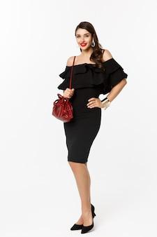 Schönheits- und modekonzept. volle länge der eleganten jungen frau, die im schwarzen kleid, in den absätzen und in der geldbörse einkaufen geht, selbstbewusst aussieht und über weißem hintergrund steht.