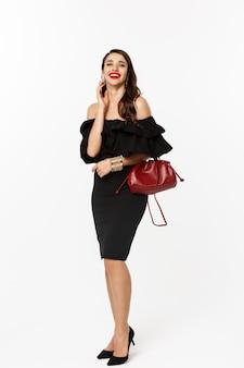 Schönheits- und modekonzept. volle länge der eleganten jungen frau im schwarzen cocktailkleid, die geldbörse hält und make-up trägt, über kamera lacht, über weißem hintergrund stehend.