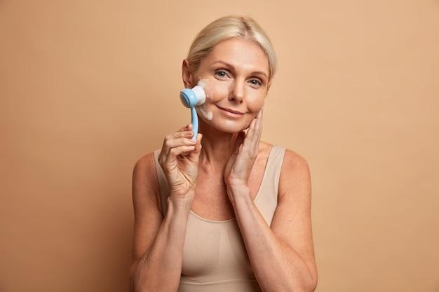 Schönheitsalter und hygienekonzept. die hübsche, faltige, ältere, blonde frau verwendet ein gesichtsmassagegerät und wäscht die wangen mit schaumstoff, der in ein lässiges oberteil gekleidet ist. sie hat eine perfekte, gesunde haut
