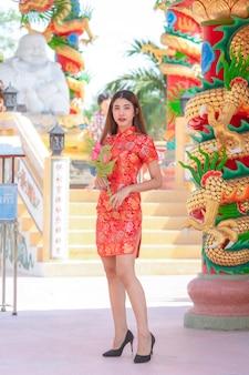 Schönheitsasiat, der rotes kleid im chinesischen neujahrsfest trägt