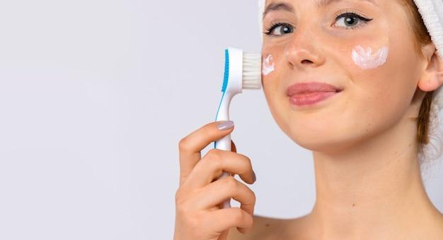 Schönheitsbehandlungen und gesichtspflege. eine frau mit einem handtuch auf dem kopf und creme auf den wangen macht eine massage mit einer kosmetikbürste. foto auf weißer wand. hochwertiges foto