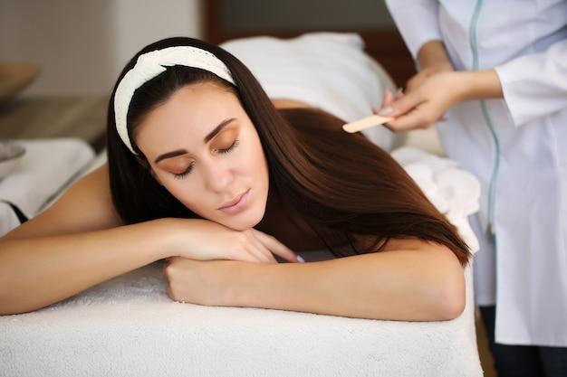 Schönheitsbehandlungskonzept. spa für körper, gesundheit und entspannung, spa-center. der masseur massiert den weiblichen körper.