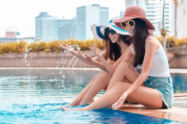 Schönheitsbikini in der sonnenbrille, die wasserspritzen spielt und trinken cocktails nahe pool.