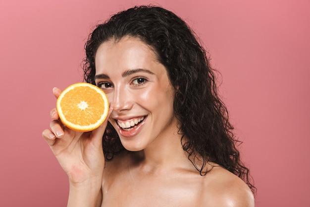 Schönheitsbild der bezaubernden halbnackten frau mit dem langen haar, das lächelt und stück orange hält, lokalisiert über rosa hintergrund