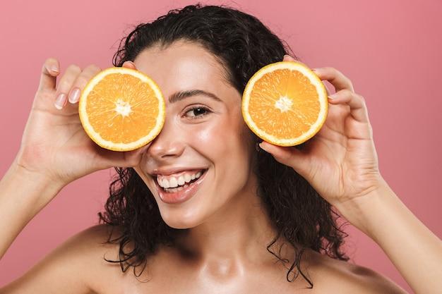 Schönheitsbild der europäischen halbnackten frau mit den langen haaren, die lächeln und stücke der orange halten, lokalisiert über rosa hintergrund